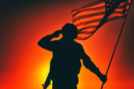 Silhouette of army soldier, armed service rifle, holding USA national flag, saluting on background of sunset or dawn sky. Military respect and honor, patriotism veterans and heroes remembrance 写真素材