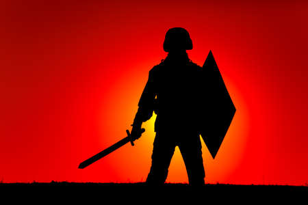 Silhouette of modern soldier in combat helmet, armed sword and shield, standing on background of sunset sky and sun setting behind horizon. Army heroism, state defender and patriotism concept