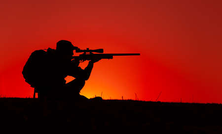 Commando team sniper, army special forces shooter aiming, shooting sniper rifle while sitting on sea or ocean shore during sunset. Coast or border guard soldier observing coastline with optical sight
