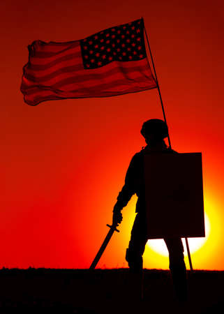 Silhouette of American army soldier armed sword and shield standing under waving US national flag on background of sunset. Army hero and patriot, military glory and honor, fallen soldiers remembrance Banque d'images