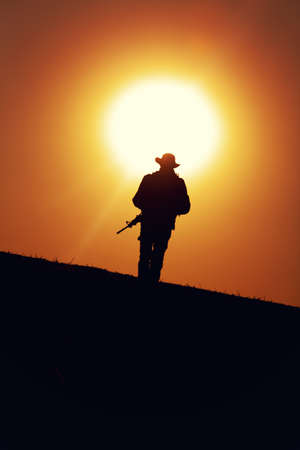 Silhouette of army special forces soldier armed with service rifle, commando, counter terrorist team fighter in boonie hat and uniform marching during mission, patrolling area on sunset or dawn time Banque d'images