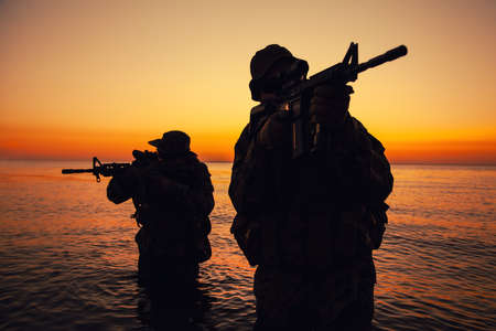 Two commando soldiers, army special operations fighters aiming assault rifles while coming out from water on shore at sunset or dawn. Coast guard shooters landing on sea coast, sneaking in water Banque d'images