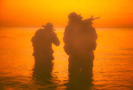 Commando soldiers walking in water, army special operations forces fighters sneaking in darkness, aiming assault rifles and observing shore during amphibious operation on coast at night or dawn Banque d'images