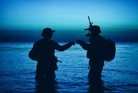 Army special operations forces soldiers, commando fighters doing fist dump gesture while standing knee-deep in water. Two Marines shooters or coast guard fighters celebrating mission successful ending