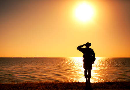 Silhouette of saluting commando soldier, army infantryman standing on shore during sunset or sunrise. Military solemn ceremony, respectable salute for honoring fallen heroes and comrades veterans