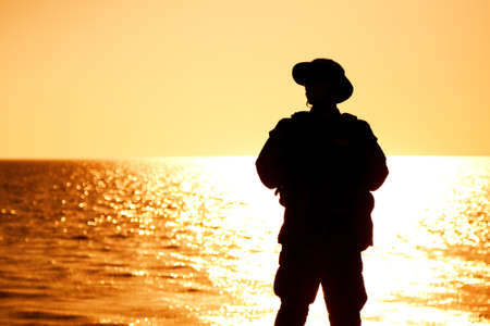 Silhouette of army infantry soldier, coast guard fighter in boonie hat, standing on shore, sunset and ocean horizon on background. Border guard service soldier patrolling coastline, standing on beach