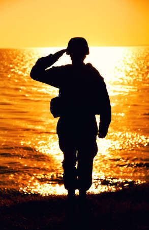 Silhouette of army soldier, Marines fighter in helmet and ammunition saluting while standing on seashore at sunset time. Coast guard fighter, special operations forces soldier honoring fallen comrades