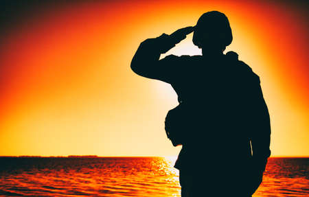 Silhouette of soldier in combat helmet and ammunition saluting on background of sunset sky. Army special forces fighter, Marines rifleman showing respect, greeting officer with salute gesture