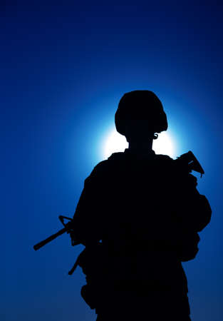 Silhouette of army infantry soldier armed assault rifle on background of night sky with moon. Special operations forces fighter in combat helmet and uniform during night mission, military sentry duty