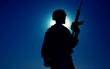 Silhouette of army soldier standing with service rifle in hand on background of night sky with moon. Armed Marines infantry in battle helmet and uniform ready for action, patrolling area in darkness