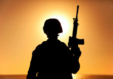 Silhouette of army soldier, special operations forces infantry rifleman, Marines fighter in combat helmet and ammunition standing with assault rifle in hand on background of sunset or dawn sky Banque d'images