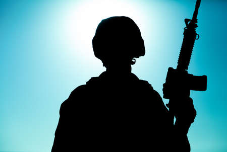 Silhouette of army soldier, special operations forces infantry rifleman, Marines fighter in combat helmet and ammunition standing with assault rifle in hand on background of sunset or dawn sky