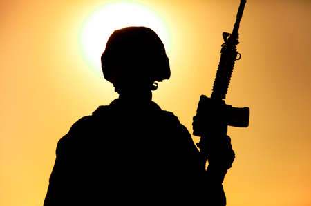 Silhouette of army soldier, special operations forces infantry rifleman, Marines fighter in combat helmet and ammunition standing with assault rifle in hand on background of sunset or dawn sky Foto de archivo