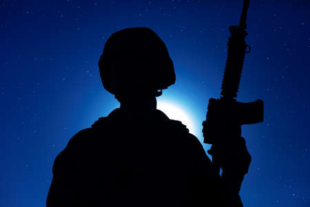 Night silhouette of army special operations forces soldier standing with service rifle on background of night sky with moon and stars. Modern warfare combatant in helmet, Marines raider in darkness Banque d'images