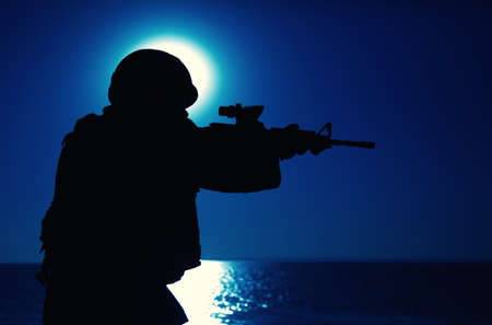 Silhouette of army special forces rifleman, soldier in ammunition and helmet aiming gun, shooting with service rifle on seacoast at night. Commando fighter, marine raider during amphibious mission