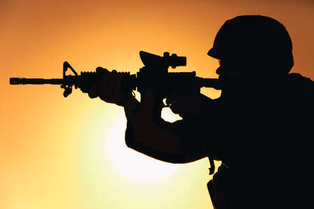 Silhouette of modern army infantry soldier standing on background of setting sun and aiming assault rifle with collimator sight. Special operations rifleman, elite forces shooter shooting in enemy
