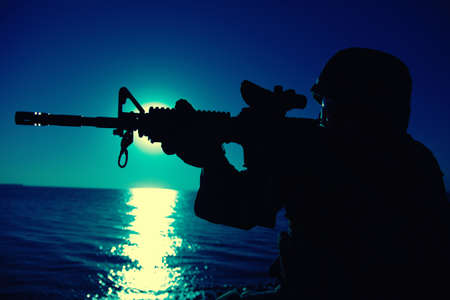 Modern army infantry soldier, coast guard rifleman aiming assault rifle with collimator sight at night. Special operations forces fighter engaging enemy in darkness, observing territory during mission