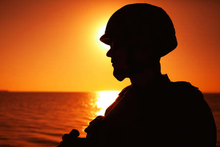 Silhouette of army infantry soldier, special forces rifleman armed with service rifle, patrolling coastline at sunset. Coast guard fighter in combat helmet and tactical ammunition standing on seashore Foto de archivo
