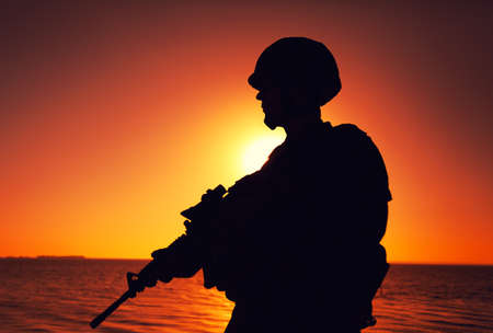 Silhouette of army infantry soldier, special forces rifleman armed with service rifle, patrolling coastline at sunset. Coast guard fighter in combat helmet and tactical ammunition standing on seashore Banque d'images