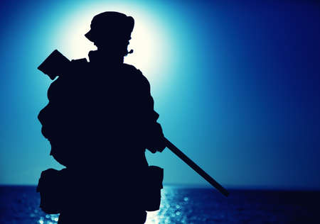 Silhouette of army elite forces fighter standing with sniper rifle on background of blue sky with moon or sun. Sniper or marksman in boonie hat, carrying backpack on mission, patrolling at night Banque d'images
