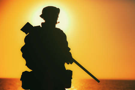 Silhouette of army elite forces sniper, commando shooter in boonie hat, carrying backpack, equipped tactical radio, walking on background of setting or raising sun. Counter terrorist forces soldier