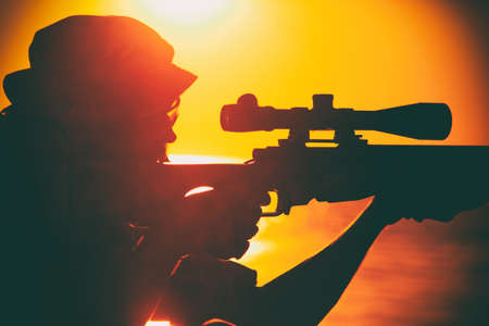 Commando team sniper, army special forces shooter aiming, shooting sniper rifle while sitting on sea or ocean shore during sunset. Coast or border guard soldier observing coastline with optical sight Banque d'images
