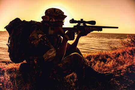 Commando team sniper, army special forces shooter aiming, shooting sniper rifle while sitting on sea or ocean shore during sunset. Coast or border guard soldier observing coastline with optical sight Foto de archivo