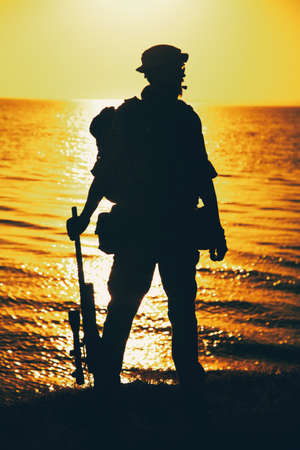 Silhouette of army commando fighter, Navy SEALS team sniper or coast guard soldier standing on sea shore with rifle on background of ocean sunset horizon. Special forces rifleman patrolling coastline