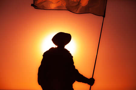 Silhouette of army soldier, commando fighter special forces infantryman standing on background of sunset sky waving on flagpole flag. Military victory, remembrance of fallen soldiers, veterans concept