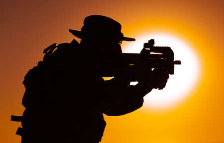 Silhouette of army special forces commando, soldier in boonie hat aiming and shooting bullpup submachine gun on background of setting sun. Private military company mercenary engaging enemy at sunset
