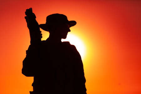 Silhouette of army special forces soldier in boonie and ballistic goggles, standing with bullpup submachine gun on background of sunset sky. Commando fighter, elite forces rifleman patrolling on dawn