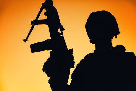 Shoulder silhouette of army machine gunner, special operations forces infantryman standing with raised gun on background of sunset sky. Marine Corps shooter in combat helmet holding weapon at dawn Banque d'images