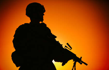 Silhouette of army infantry soldier, commando in combat helmet, armed light machine gun, standing on background of ocean horizon and sunset. Marine Corps rifleman, special forces shooter on sea shore