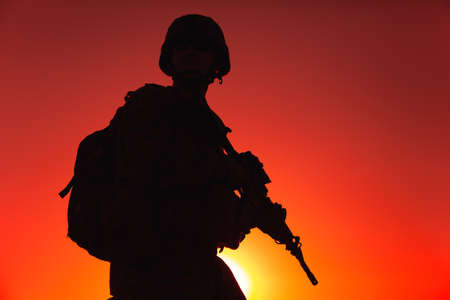 Silhouette of army rifleman in helmet and ammunition, carrying tactical backpack, walking with service rifle on background of sunset sky. Counter terrorist forces fighter marching at night mission Foto de archivo