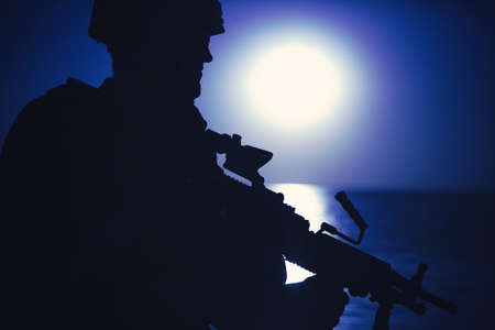 Silhouette of army infantryman standing with light machine gun on background of night sky with moon. Commando soldier in ammunition patrolling coastline, sneaking in darkness during night mission
