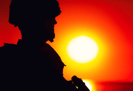 Shoulder silhouette of army soldier, special operations forces fighter in combat helmet and ballistic glasses, standing with gun on background of setting below ocean horizon sun