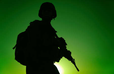 Silhouette of army rifleman in helmet and ammunition, carrying tactical backpack, walking with service rifle on background of sunset sky. Counter terrorist forces fighter marching at night mission