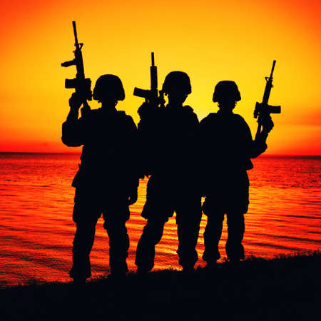 Silhouette of army special operations forces soldiers team, group of Marines or coast guard fighters crew in ammunition and combat helmets standing on seashore at sunset with raised assault rifles Banque d'images
