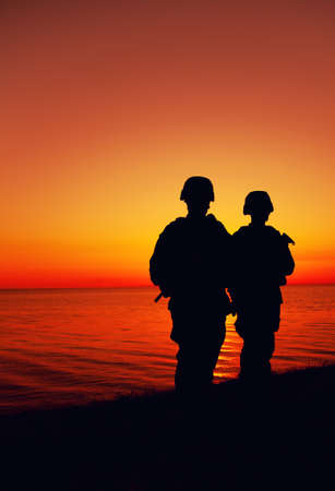 Silhouette of two Marines soldiers, special operations infantrymen or coast guard fighters in uniform and combat helmet, armed service rifles, standing on seashore, patrolling beach at sunset or dawn