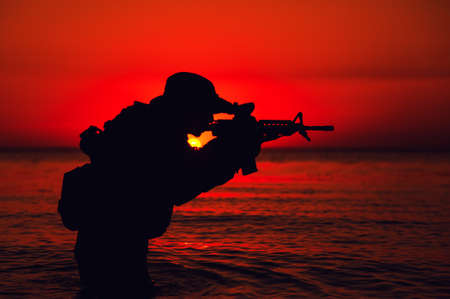 Silhouette of army soldier aiming and shooting service rifle while standing knee-deep in sea water. Coast guard, naval forces soldier attacking enemy with weapon, landing on beach on sunset or dawn