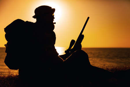 Silhouette of commando fighter, army special forces sniper sitting on sea or ocean shore on sunset. Coast guard rifleman observing beach, resting during coastline patrol or amphibious operation Banque d'images