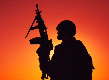 Silhouette of army soldier, special operations shooter armed light machine gun standing on background of ocean or sea horizon at sunset time. Coast guard machine gunner on beach, patrolling coastline