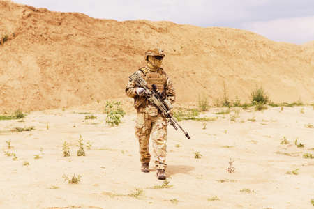 Equipped special forces soldier walks across desert. Anti-terror operation concept.