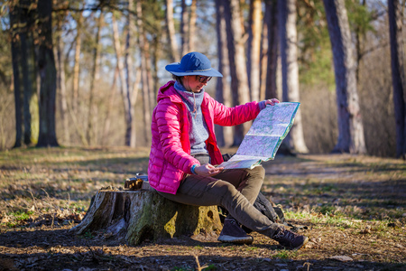 female tourist in the forest looks at a map