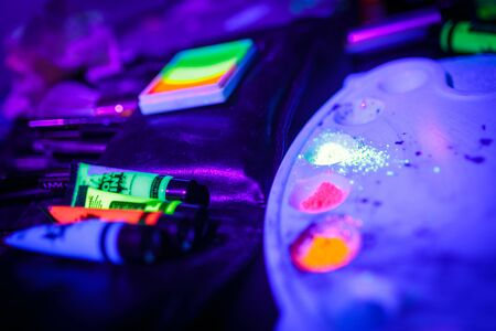 Multicolored UV fluorescent powder and paints on a palette