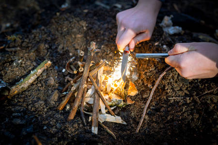 Outdoors makeing fire by flint. Closeup view.