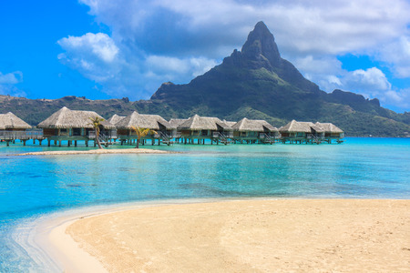 bungalow: overwater bungalow in front of the mountain Stock Photo