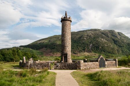 The old tower in Scotland, called Glenfinnan Monument, lies on the lake in the mountains.