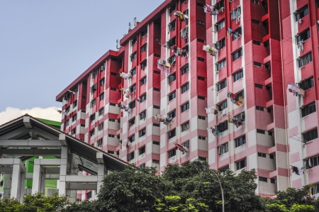 Apartment Blocks in Singapore showing high rise concrete buildings with a red colour schemes  Washing can be seen hanging from the windows  A more modern architecturally designed building can be seen the foreground Stock Photo - 20345402