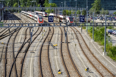 overbridge: Scenes from an overbridge in the Swiss city of Geneva showing rails, trains, and track structures. 3 trains are shown waiting Stock Photo